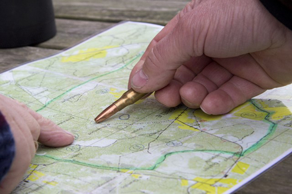 På ett bord ligger en karta, två händer pekar på kartan, den ena handen pekar på kartan med en tomhylsa.
