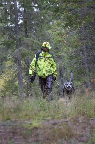 En man med jaktkläder och ett vapen på axeln går med en jakthund i skogen.