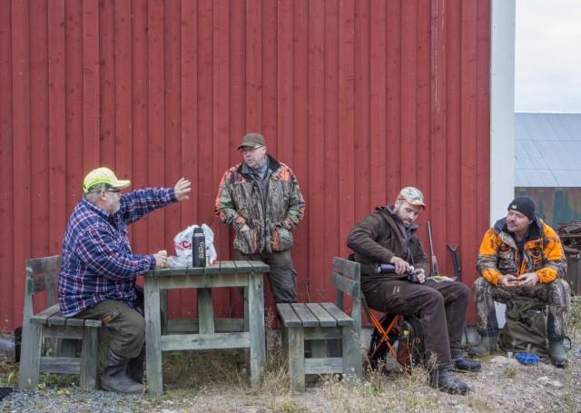 Fyra män i jaktkläder sitter ner och dricker kaffe